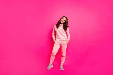 Full length body size photo toothy beaming smiling amazing she her lady hands arms in pockets self-confident wearing modern casual pink costume suit pullover outfit isolated vibrant rose background Stock Photo