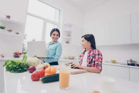 Portrait of two nice cute lovely attractive adorable cheerful cheery people mommy mom working remotely girl making salad in light white kitchen interior