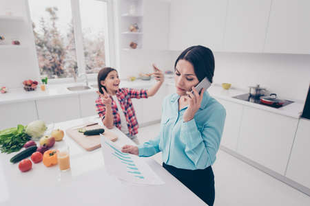 Portrait of two nice lovely sweet attractive cheerful cheery people mommy mom talking on cell girl making selfie showing v-sign in light white kitchen interior