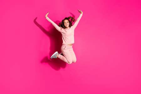 Foto de tamaño de cuerpo de cuerpo entero, ojos cerrados, salto alto, increíble, ella, sus manos de dama, brazos, ayudan a volar los brazos hacia arriba, como un niño con traje casual rosa, traje, traje, aislado, vibrante, rosa, fondo