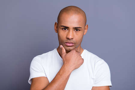 Close up photo amazing dark skin he him his man groomed shaved face hand arm on chin contemplation overthinking wearing white t-shirt outfit clothes isolated on grey background. Foto de archivo