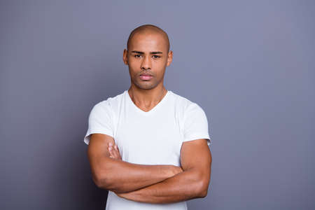 Close up photo strong healthy masculine dark skin he him his macho bald head arms crossed strict look on camera overthinking wearing white t-shirt outfit clothes isolated grey background.