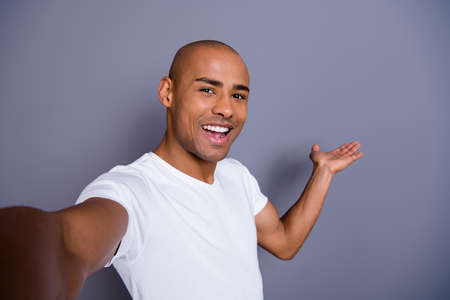 Close up photo healthy masculine dark skin he him his macho bald head make take selfies video translation blog show way for foreigners wearing white t-shirt outfit clothes isolated grey background.