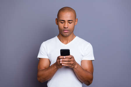 Close up photo strong healthy dark skin he him his macho bald head telephone arms reader not smiling looking political sports news wearing white t-shirt outfit clothes isolated grey background.