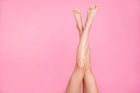 Bijgesneden close-up afbeelding Bekijk foto van mooie perfecte lange aantrekkelijke vrouwelijke pasvorm dunne slanke zachte gladde glans geschoren benen advertentie geïsoleerd over roze pastel achtergrond Stockfoto