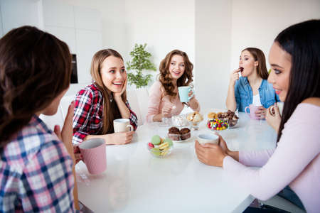 Close up portrait attractive cute beautiful she her diversity ladies sit round white table hold cups hot beverage speak over news friends girls day night holiday indoors