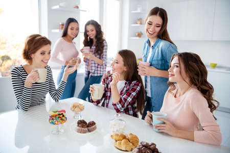 Close up portrait beautiful she her ladies missed family meeting sister cousins stand sit round big white table bright kitchen hold cups share novelty emotional girls day night holiday Archivio Fotografico