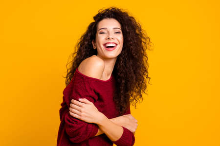 Close up side profile photo amazing beautiful her she lady beaming toothy smiling holding herself hugs self-confident wearing red knitted sweater pullover clothes outfit isolated yellow background Stock Photo