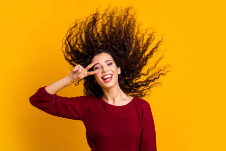 Close up photo amazing charming her she lady hair flight show v-sign near eye careless cheerful funky playful wearing red knitted sweater clothes outfit isolated yellow bright background 写真素材