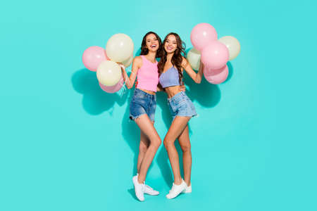 Full length body size photo beautiful cheerful two she her ladies colorful balloons hands arms festive nice thin hips wearing shiny jeans denim shorts tank tops isolated teal bright vivid background 免版税图像 - 118003522