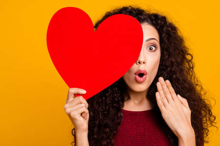 Close-up portrait of nice cute lovely attractive cheerful cheery funny wavy-haired lady holding in hand hiding behind big heart shape isolated over bright vivid shine background 写真素材