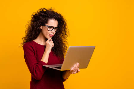 Portrait of her she nice cute clever smart attractive pretty minded focused unsure wavy-haired lady holding in hands laptop touching chin isolated over bright vivid shine orange background