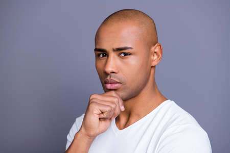 Close up photo not sure dark skin he him his man good-looking groomed shaved face hand arm on chin contemplation overthinking wearing white t-shirt outfit clothes isolated on grey background 写真素材