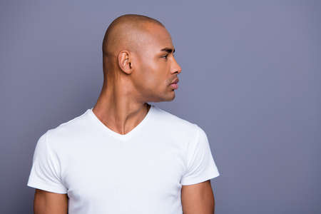Close up photo amazing dark skin he him his man head turned to empty space distracted smart clever eyes shiny shaved face wearing white t-shirt outfit clothes isolated on grey background Reklamní fotografie