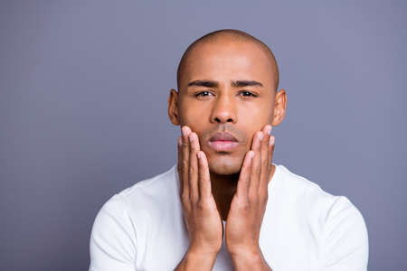 Close up photo dark skin he him his man strict check skin after shaving hand arm on cheeks cheekbones comparing overthinking wearing white t-shirt outfit clothes isolated on grey background Stok Fotoğraf
