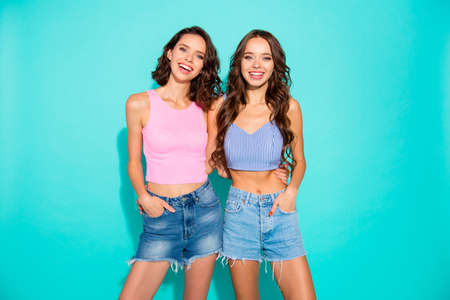 Close up portrait two stunning beautiful confident she her lady chic hugging revealing white teeth toothy wearing pink jeans denim shorts tank tops isolated blue teal bright vivid background