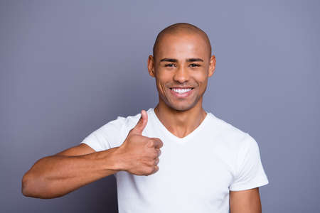 Close up photo glad toothy dark skin he him his macho bald head approve show big thumb finger advise buy buyer new product wearing white t-shirt outfit clothes isolated on grey background 스톡 콘텐츠