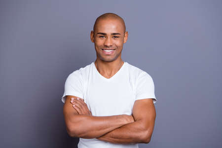 Close up photo attractive strong healthy masculine dark skin he him his macho bald head arms crossed kindhearted toothy smiling wearing white t-shirt outfit clothes isolated grey background