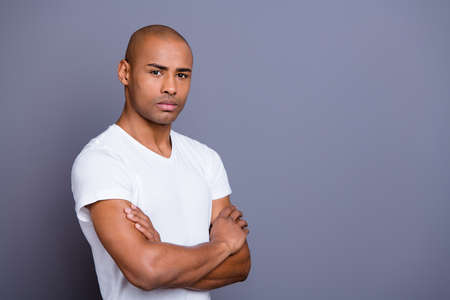Close up photo attractive strong healthy masculine dark skin he him his macho bald head arms crossed overthinking dislike something wearing white t-shirt outfit clothes isolated grey background
