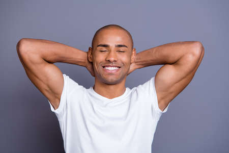 Close up photo calm healthy masculine dark skin he him his macho bald head arms behind eyes closed sit on brunch near seaside fresh air wearing white t-shirt outfit clothes isolated grey background