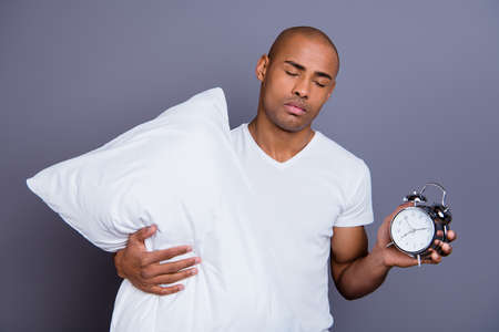 Close up photo sick mad unhealthy dark skin he him his macho bald head hold clock pillow sleep and walk sleepless night wearing white t-shirt outfit clothes isolated grey background Stock Photo