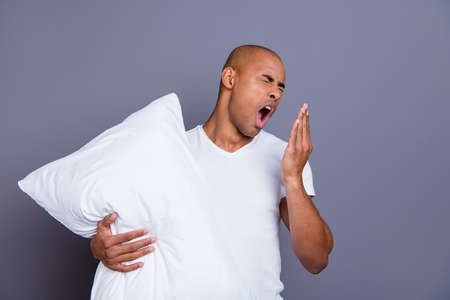 Close up photo unhealthy dark skin he him his macho bald head tired yawn yell scream shout hold pillow sleep and walk sleepless night wearing white t-shirt outfit clothes isolated grey background Stock Photo