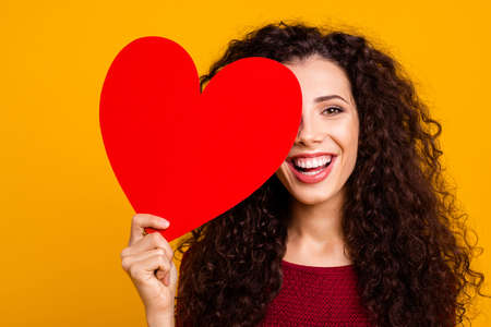 Close-up portrait of nice cute adorable attractive cheerful positive wavy-haired lady holding in hand hiding eye behind heart shape cardiac cardiology isolated over bright vivid shine background