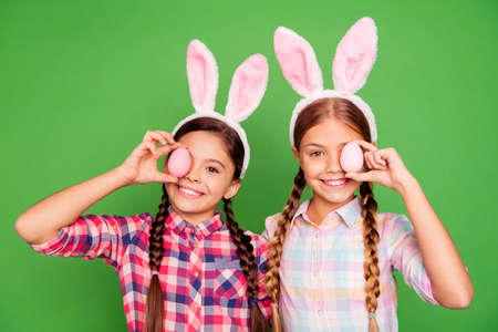 Close up photo of two pretty little age girls holiday concept with bunny ears on head hiding one eye behind easter colored eggs wearing casual checkered plaid shirts isolated on green background Stock Photo