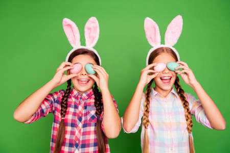 Closeup photo of two cute sweet lovely with open mouth long haired in checkered casual shirt outfit holding colorful eggs in hands isolated bright vibrant background Stock Photo