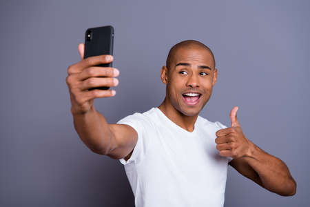 Close up photo healthy dark skin he him his macho short hairdo thumb up make take selfies excited video call glad opened mouth wearing white t-shirt outfit clothes isolated grey background