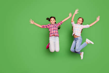Full length body size photo two little age she her girls hand arm up jump high school competition cheerleaders wear casual jeans denim checkered plaid shirts isolated green vibrant vivid background