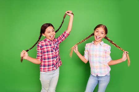 Portrait of two nice sweet cute lovely funny cheerful cheery positive pre-teen girls wearing checked shirt having fun playing with tails isolated over bright vivid shine green background