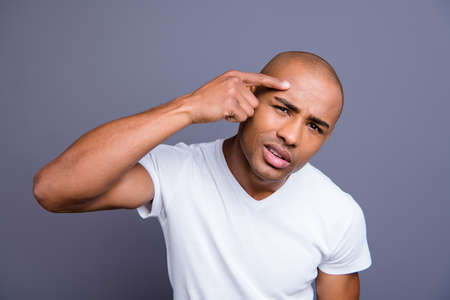 Close up photo dark skin he him his macho expertise skin hand arm on forehead not sure about action anti aging cream moisturizer wearing white t-shirt outfit clothes isolated on grey background