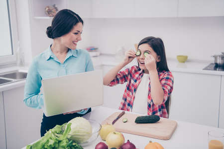 Portrait of two nice cute lovely attractive sweet adorable cheerful people girl fooling closing covering eyes with fresh cucumber pieces in light white kitchen interior indoors Stock Photo
