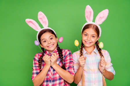 Close up photo of charming with beaming toothy smile white caucasian latin hispanic kids school girls holding colorful eggs in hands isolated bright vivid background Stock Photo