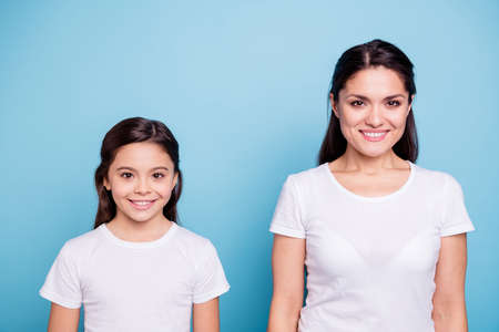 Close up photo two people brown haired mum and small daughter standing straight looking to camera wearing white t-shirts isolated on bright blue background