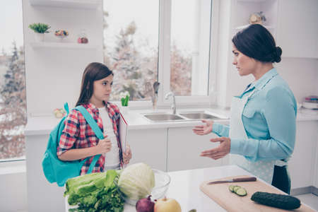 Profile side view portrait of two nice lovely sweet attractive confused puzzled sad people mommy mom pre-teen girl got bad marks in light white kitchen interior