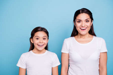 Close up photo pretty two people brown haired mum small little daughter eyes mouth opened facial expression delighted sale discount wearing white t-shirts isolated bright blue background