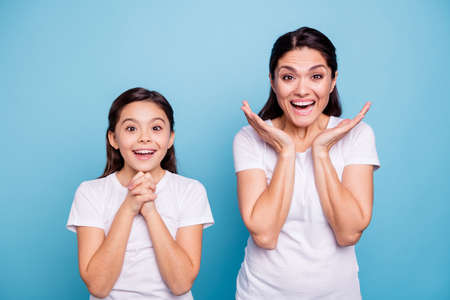 Close up photo pretty two people brown haired mum little daughter eyes mouth opened unbelievable yelling praying arms in air together wearing white t-shirts isolated bright blue background Stock Photo