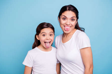 Close up photo beautiful two people brown haired mom little daughter friends hipsters silly mouth opened tongue out fooling around playing wear white t-shirts isolated bright blue background