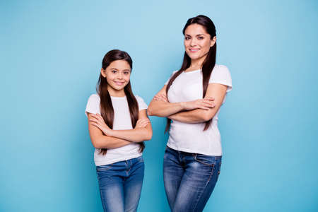 Close up photo pretty two people brown haired mum small little daughter crossed arms self-confidently stand opposite ready win winner family games victory wear t-shirts isolated bright blue background