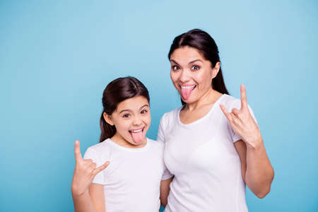 Close up photo beautiful two people brown haired mom little daughter friends hipsters mouth opened tongue out rock music lovers amazed wear white t-shirts isolated bright blue background Stockfoto