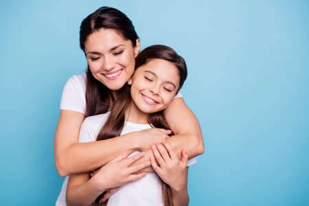 Close up photo pretty two people brown haired mum small little daughter stand hugging piggy back lovely close eyes free time rejoice wearing white t-shirts isolated on bright blue background