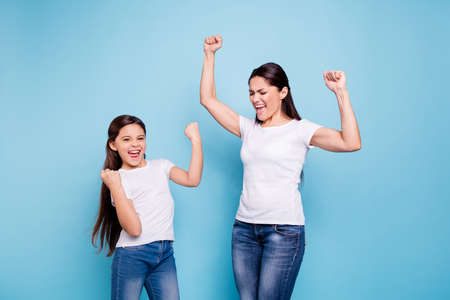 Close up photo cheer pretty two people brown haired mum small little daughter  arms up in air gladly yelling family games victory wear white t-shirts isolated bright blue background