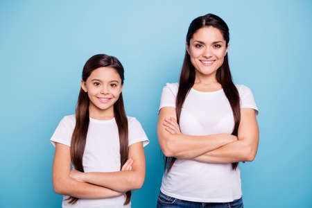 Close up photo pretty two people brown haired mum small little daughter crossed arms self-confidently standing ready win winner family competitions wear white t-shirts isolated bright blue background