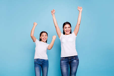 Close up photo cheer two people brown haired mum small little daughter  hands arms high in air glad yelling free sale discount shopping buy buyer wear white t-shirts isolated bright blue background