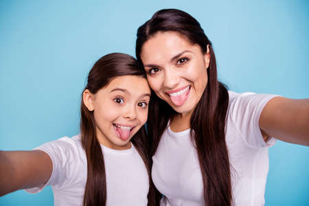 Close up photo cheer two people brown haired mum mom small little daughter make take selfies daddy wait him his he home missing tongue out of mouth wear white t-shirts isolated bright blue background