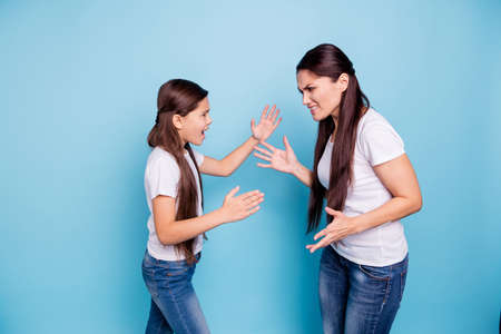 Close up side profile view photo two people brown haired mum small little daughter hands arms raised aggressive yelling fighting sick depression wear white t-shirts isolated bright blue background