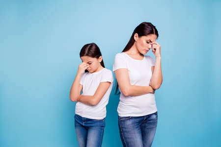 Close up photo two people brown haired mum disinterested small little daughter hand on face sick and tired sorry blaming eyes closed wear white t-shirts isolated bright blue background Stock Photo