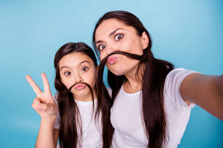 Close up photo beautiful two people brown haired mom small little daughter make take selfies moustache curls pretend guy man male show v-sign wear white t-shirts isolated bright blue background